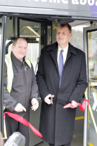 Paul Carter CBE cutting ribbon to begin electric bus trial.